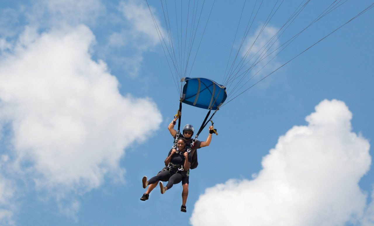 young women floats towards awesome skydive with a skydive the gulf tandem instructor