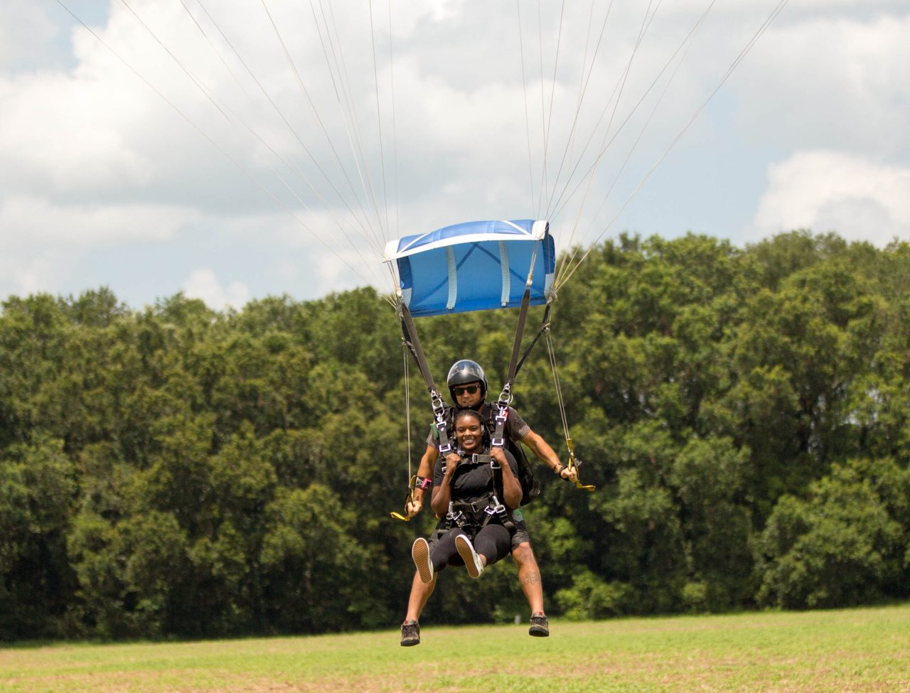 young women comes in for landing after an awesome skydive with a skydive the gulf tandem instructor