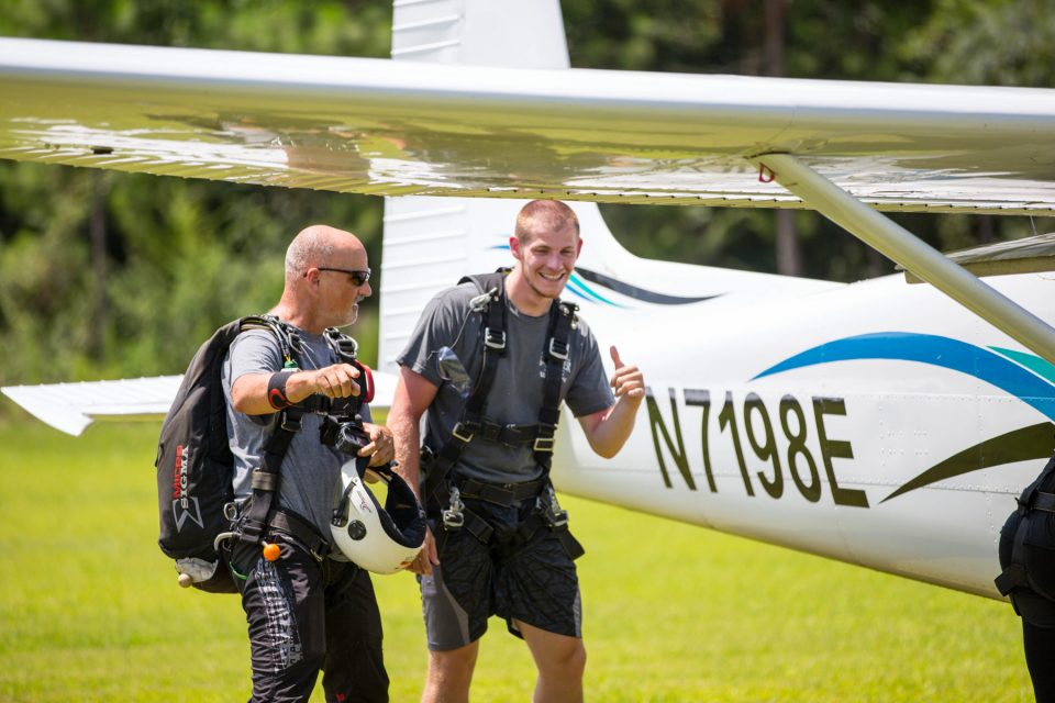 Tandem skydiver and instructor walking towards skydive the gulf aircraft