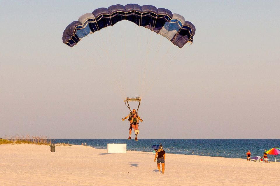 young female comes in for landing on the beach after an amazing skydive over the ocean