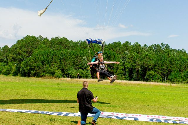 Young female comes in for landing from tandem skydive and sees will you marry me banner laid out in the grass
