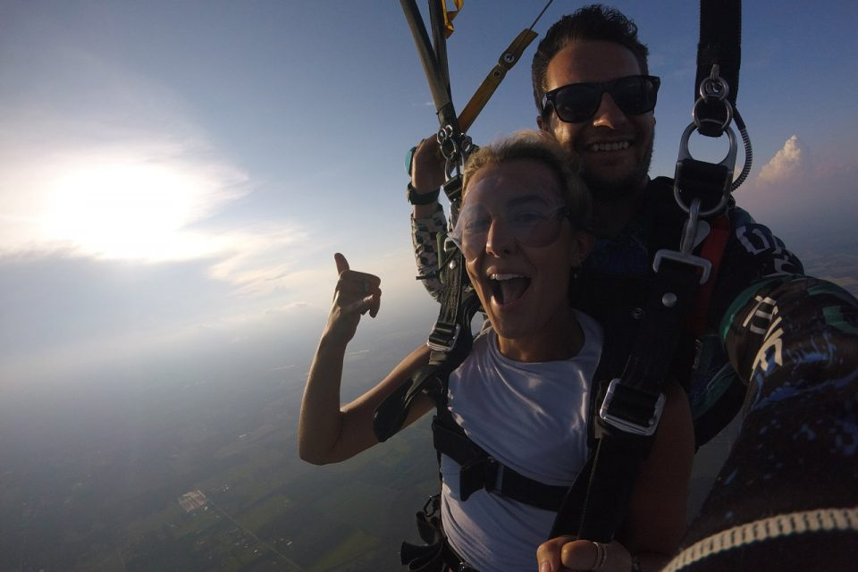 Women wearing white shirt smiling during her skydive at skydive the gulf