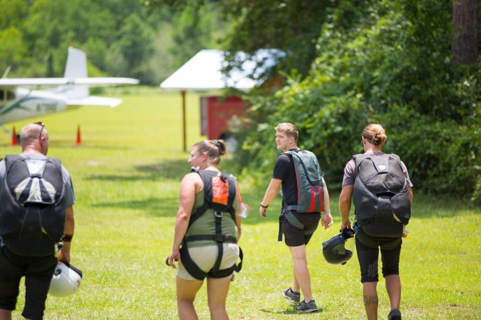 Tandem students and instructors walk towards the skydive the gulf aircraft to go for a skydive