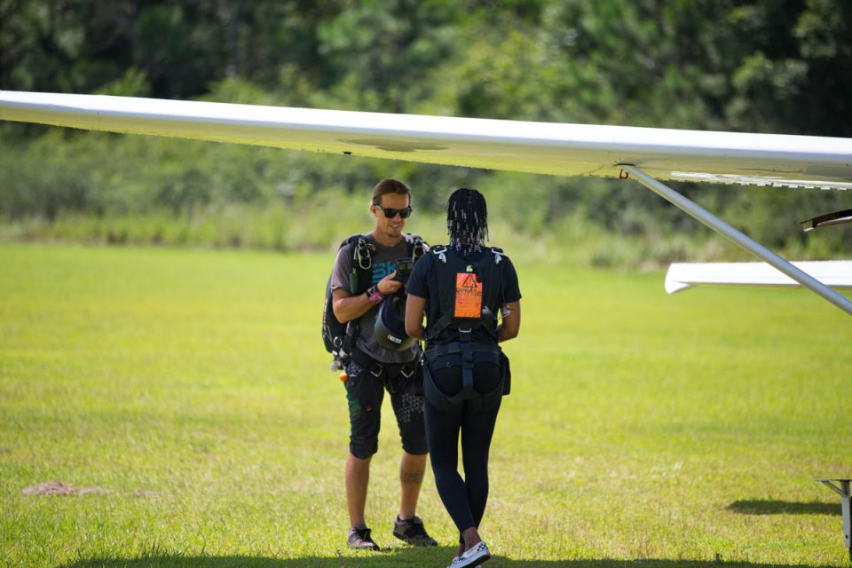 Young women walks toward the skydive the gulf aircraft before going up for a skydive