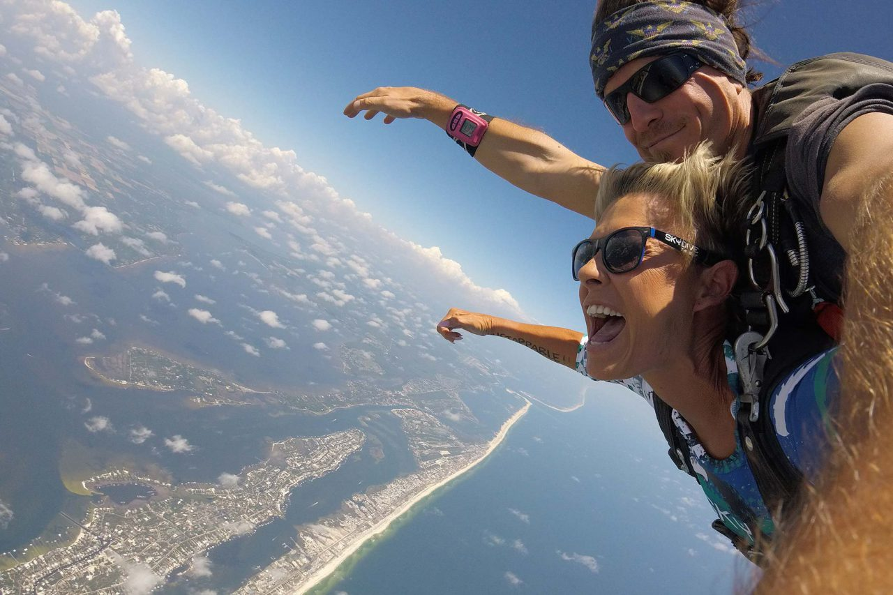 women holds her arms out and smiles while enjoying her beautiful skydive over the gulf shores