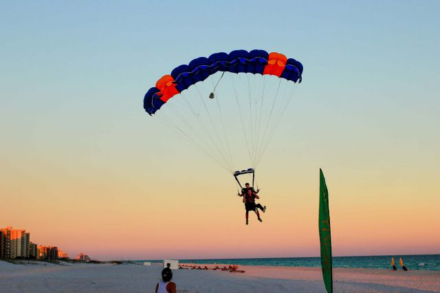 man comes in for beach landing with skydive the gulf tandem instructor