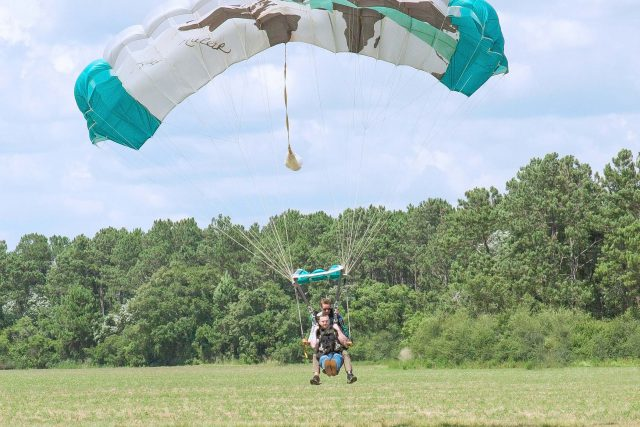 man holds his legs up as he comes in for landing from a skydive with the skydive the gulf tandem instructor
