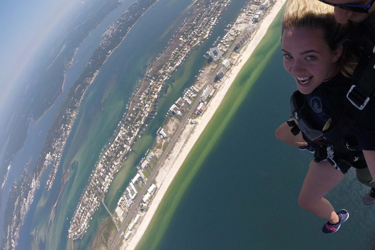 women wearing a black shirt smilies while skydiving over the beautiful gulf shores