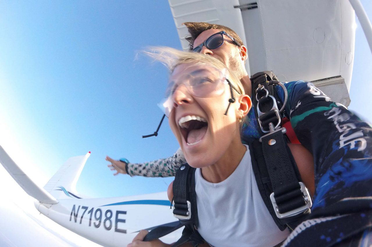 young women wearing a white shirt enjoys the rush of free fall with a skydive the gulf tandem instructor