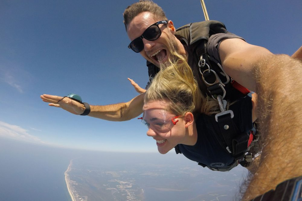Young women enjoys the beautiful views while skydiving gulf shores