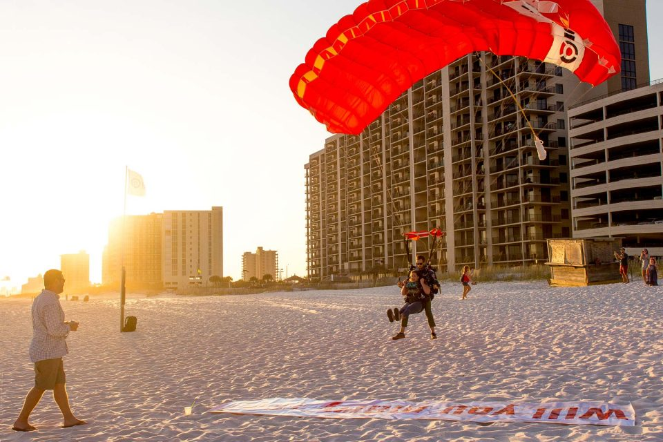 female skydiver landing on the beach right in front of a will you marry me banner laying on the beach