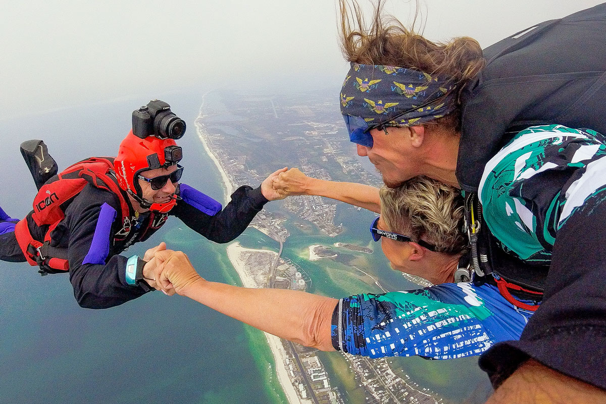 tandem skydiver and videographer holding hands during free fall portion over the ocean skydive