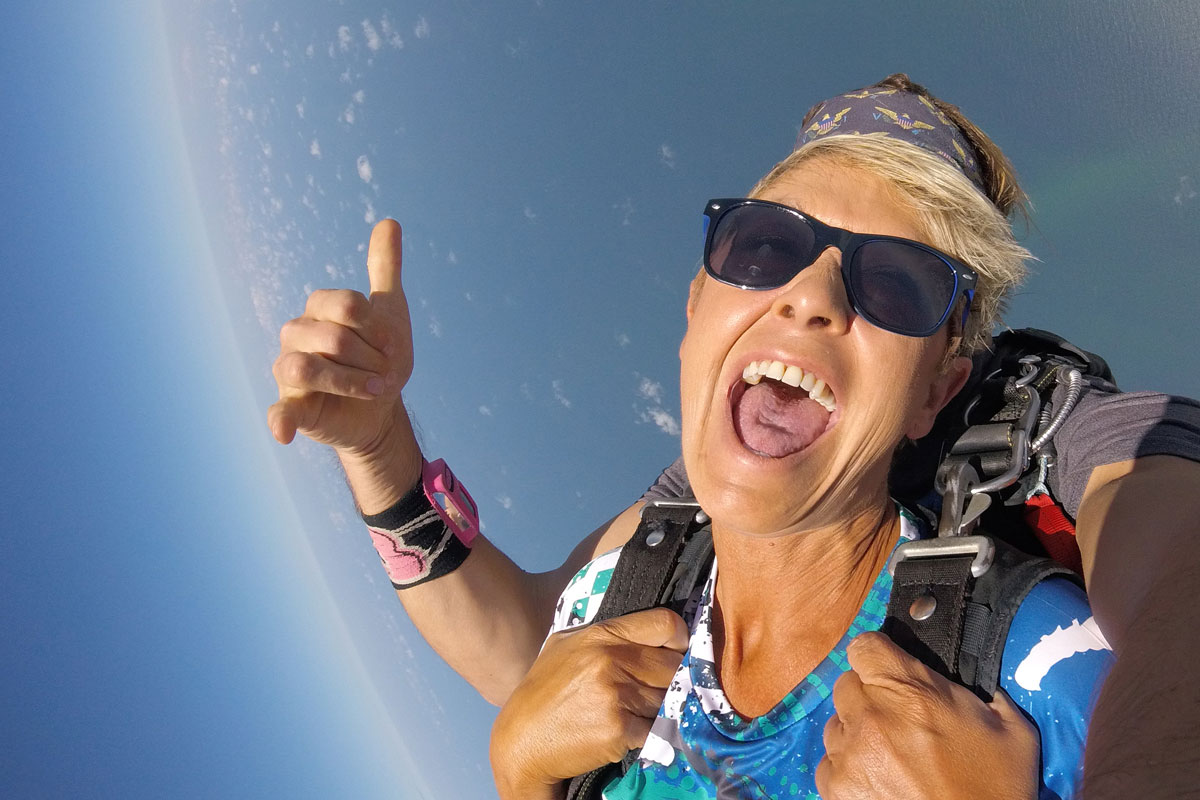 women smiles from excitement during the free fall portion of her skydive over the ocean